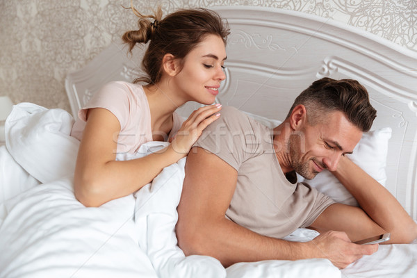 Glimlachend paar samen bed man smartphone Stockfoto © deandrobot