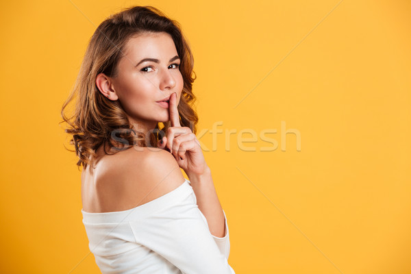 Beautiful young woman showing silence gesture. Stock photo © deandrobot