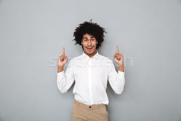 Portrait of a happy smiling african man in white shirt Stock photo © deandrobot