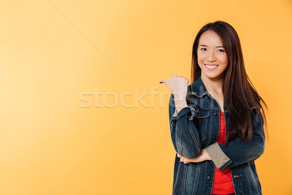 Happy asian woman in denim jacket pointing away on copyspace Stock photo © deandrobot