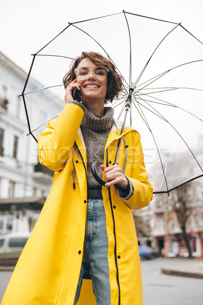 Woman in yellow raincoat and glasses talking on mobile phone hol Stock photo © deandrobot