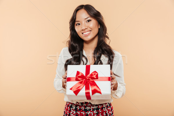 Portrait of a smiling asian woman holding gift box Stock photo © deandrobot