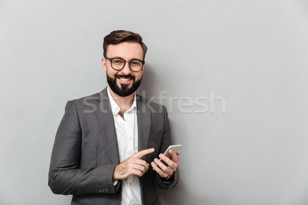 Stock photo: Smiling man in white shirt typing text message or scrolling feed