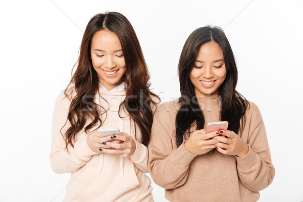 Asian pretty happy ladies sisters chatting by mobile phones. Stock photo © deandrobot