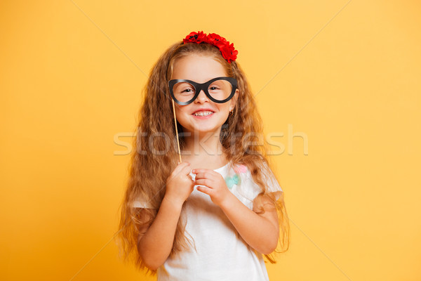 Cheerful little girl child holding fake glasses looking camera. Stock photo © deandrobot