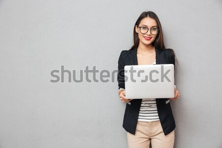 Smiling asian business woman holding laptop computer and pointing away Stock photo © deandrobot