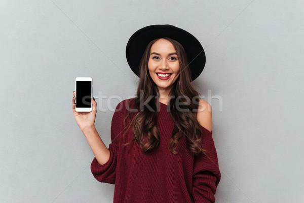Bruna donna maglione Hat smartphone Foto d'archivio © deandrobot