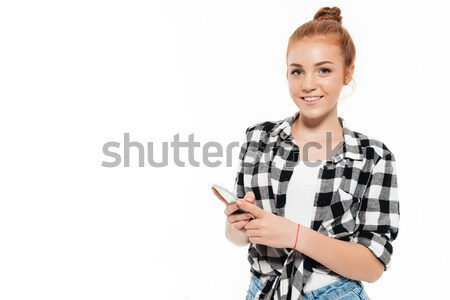 Happy ginger woman in shirt and jeans holding smartphone Stock photo © deandrobot