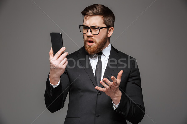 Portrait of a confused young businessman dressed in suit Stock photo © deandrobot