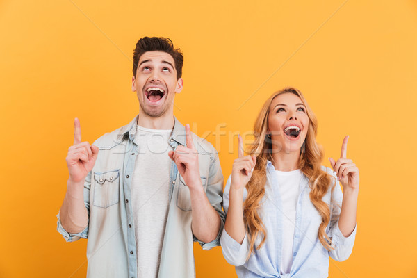 Image of excited man and woman in casual clothing smiling and lo Stock photo © deandrobot