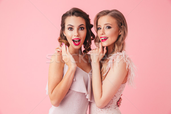 Two surprised happy elegant women in dresses standing together Stock photo © deandrobot