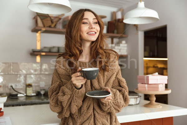 Pleased brunette woman looking aside and smiling, while drinking Stock photo © deandrobot
