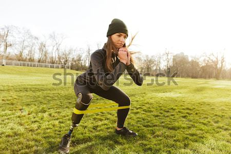 Image of happy handicapped woman 20s in tracksuit, doing sports  Stock photo © deandrobot