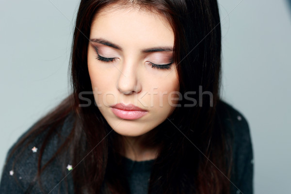 Closeup portrait of a young pensive woman with closed eyes Stock photo © deandrobot