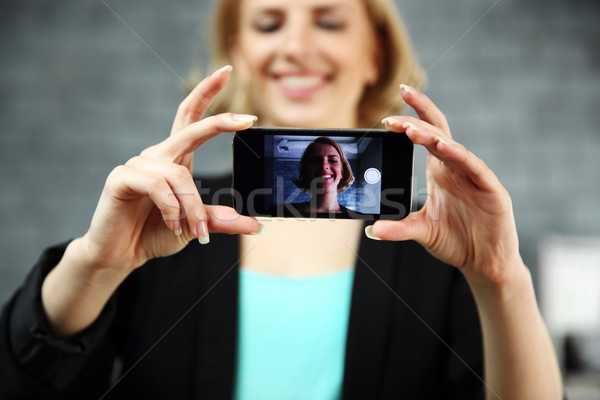 Young smiling woman making a self photo by her smartphone in office. Focus on smartphone Stock photo © deandrobot