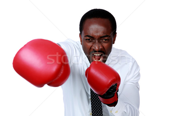 Angry businessman ready to punch you over gray background Stock photo © deandrobot