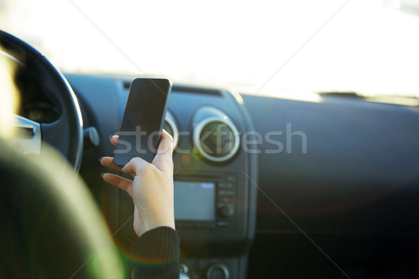 Close-up of a businesswoman sending a text while driving to work Stock photo © deandrobot