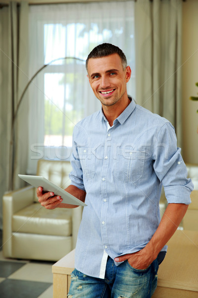 Stock photo: Happy man standing with tablet computer at home