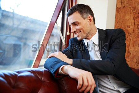 Happy businessman sitting and talking on the phone at office Stock photo © deandrobot