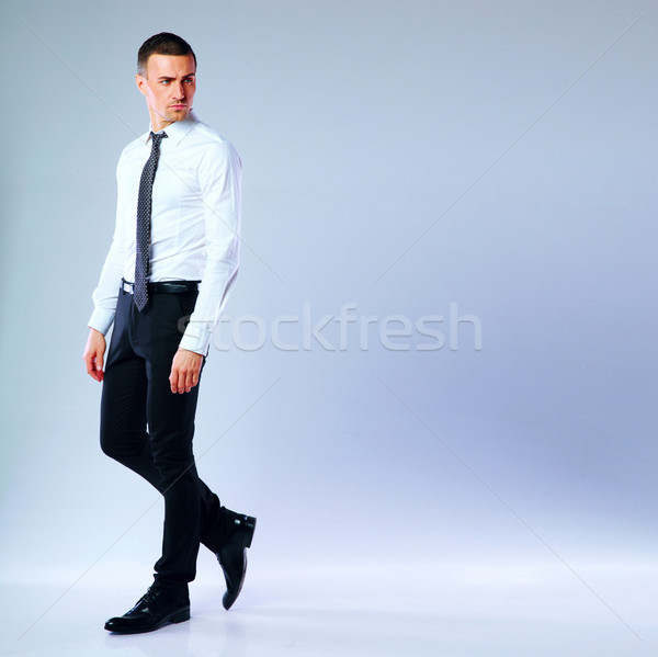Full-length portrait of thoughtful businessman on gray background Stock photo © deandrobot