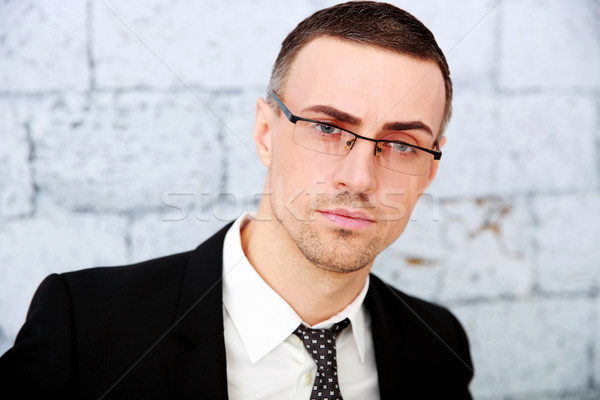 Stock photo: Handsome businessman standing near brick wall