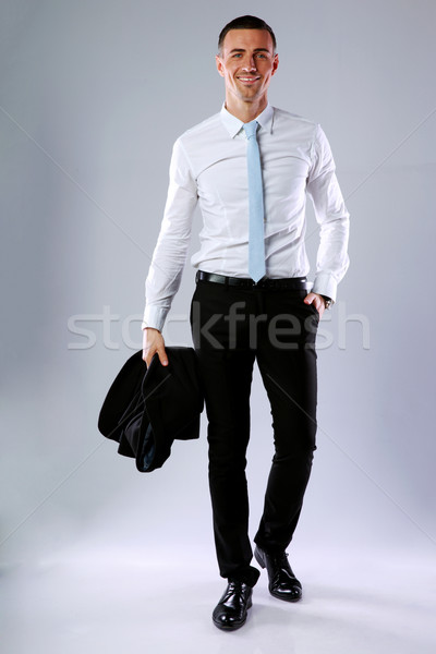 Full length portrait of a happy business man holding jacket on gray background Stock photo © deandrobot