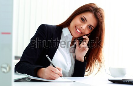 Young happy businesswoman talking on the phone and writing notes in office Stock photo © deandrobot