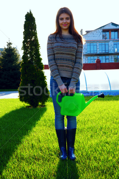 Cheerful woman standing with watering pot in garden Stock photo © deandrobot