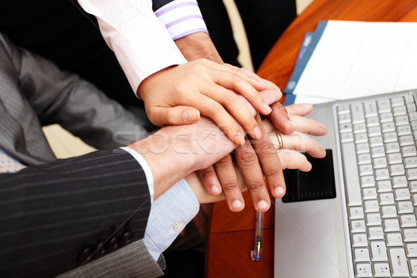 Image of business people hands on top of each other. Stock photo © deandrobot