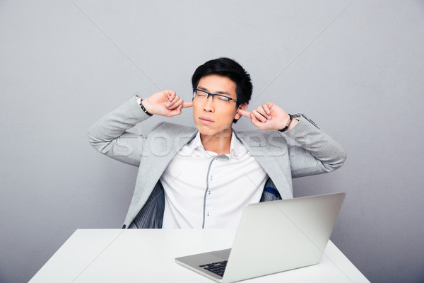 Businessman sitting at the table and covering his ears Stock photo © deandrobot