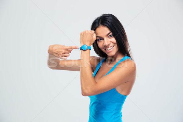 Smiling fitness woman pointing on fitness tracker Stock photo © deandrobot