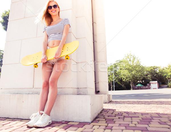 Boldog női tinédzser tart gördeszka teljes alakos Stock fotó © deandrobot