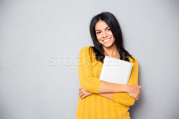 Smiling woman standing with laptop Stock photo © deandrobot