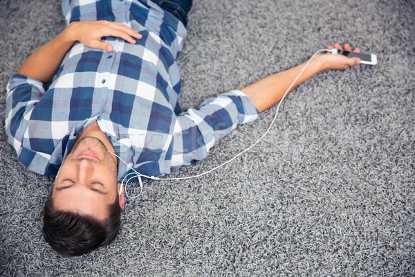Man listening music in headphones on the floor  Stock photo © deandrobot