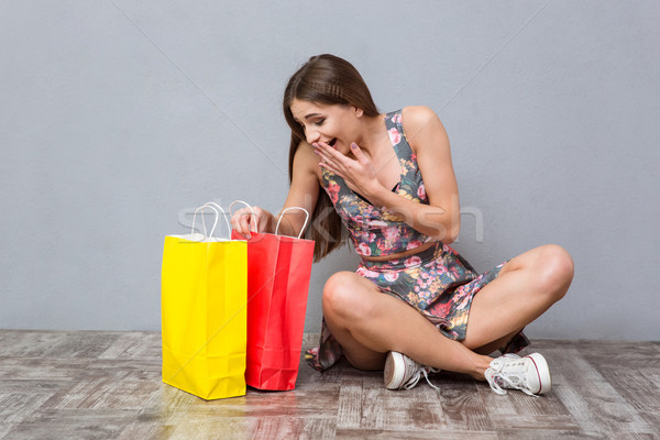 Amazed excited young woman looking into bags Stock photo © deandrobot