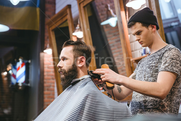 Barber making haircut to handsome man with beard  Stock photo © deandrobot