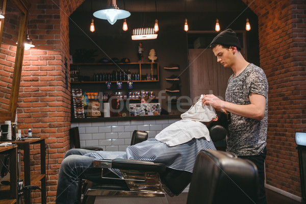 Barber finishing grooming and taking care of client's face  Stock photo © deandrobot