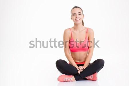 Derűs vonzó fiatal sportoló ül lábak keresztbe Stock fotó © deandrobot