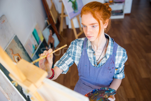 Concentrated woman painter holding art palette and painting on canvas Stock photo © deandrobot