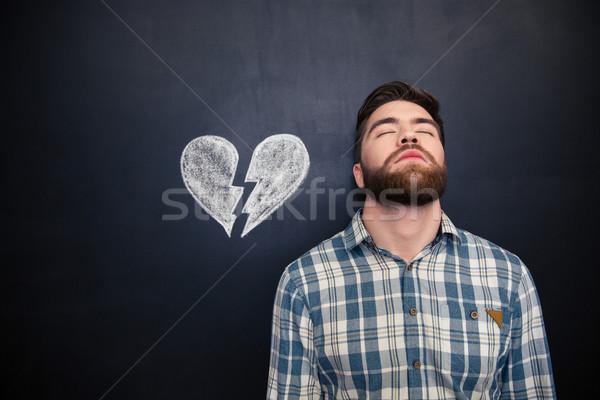 Desperate man standing over blackboard background with drawn broken heart Stock photo © deandrobot