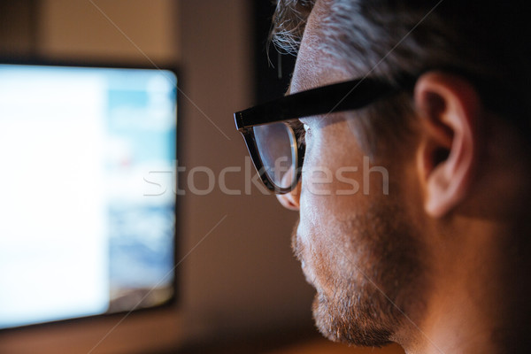 Serious man in glasses using computer and looking at screen Stock photo © deandrobot