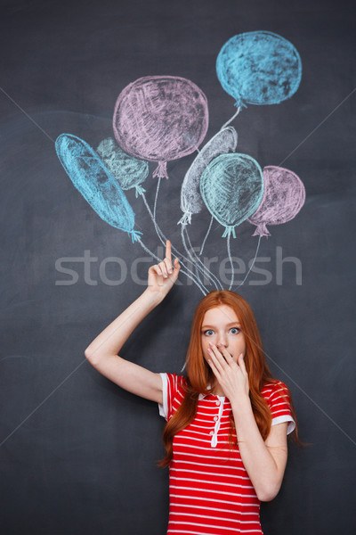 Amazed woman standing over blackboard background with drawn balloons Stock photo © deandrobot