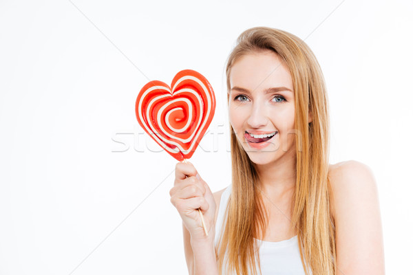 Amusing woman showing tongue and holding heart shaper lollipop  Stock photo © deandrobot