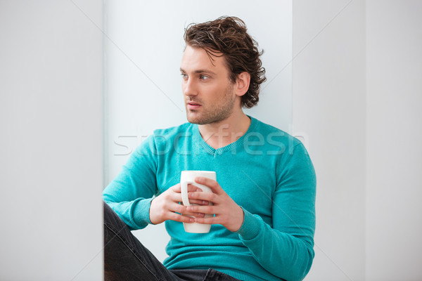 Thoughtful young man sitting on windowsill and drinking coffee  Stock photo © deandrobot