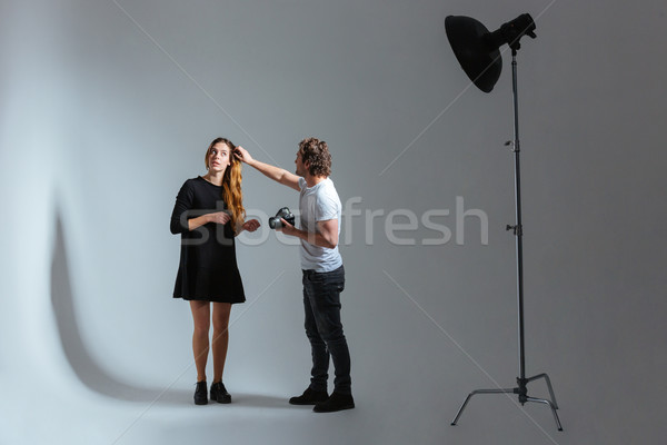 Male photographer working with female model in studio Stock photo © deandrobot