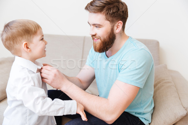 Smiling bearded young father dressing his little son Stock photo © deandrobot