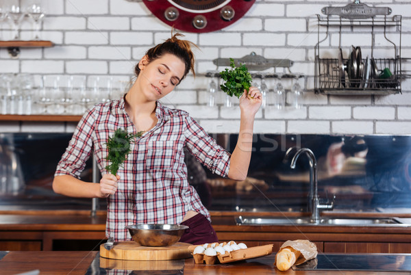 Woman with dill and parsley dacing on the kithen Stock photo © deandrobot