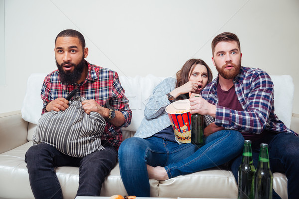 Scared friends sitting on sofa and watching tv  Stock photo © deandrobot