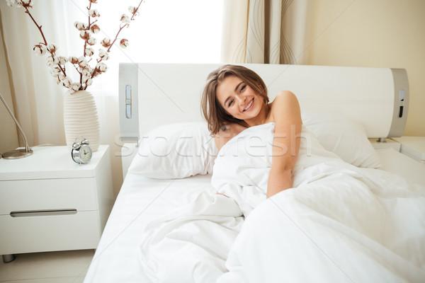 Mosolygó nő ágy pléd néz kamera otthon Stock fotó © deandrobot