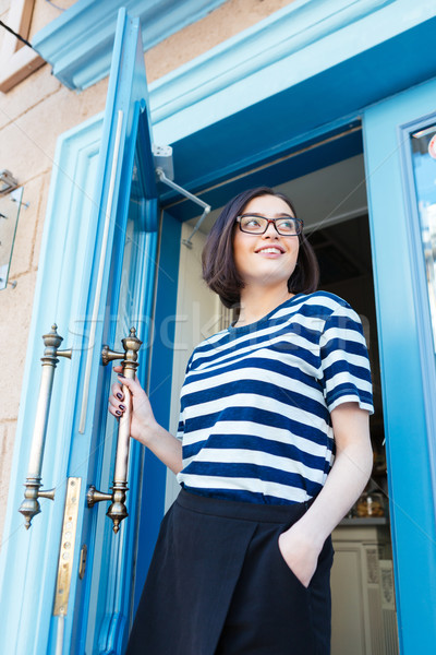 Smiling woman going out of cafe with blue door  Stock photo © deandrobot
